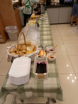 basket of rolls and slices of bread, trays, chopsticks, jam and butter