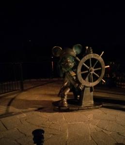 A non 25th anniversary Mickey Mouse statue at a ship's wheel
