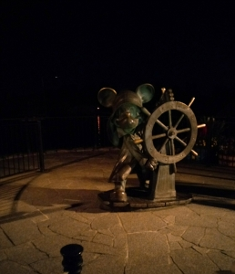 A non 25th anniversary Mickey Mouse statue at a ship's wheel