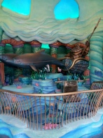 Picture of King Triton in a chariot pulled by two dolphins holding his trident at the entrance of Triton's Kingdom in the Mermaid Lagoon.