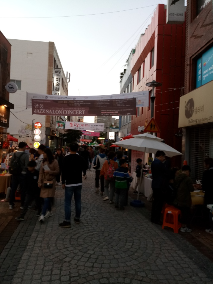 The art street busy with visitors and people participating in mini workshops.